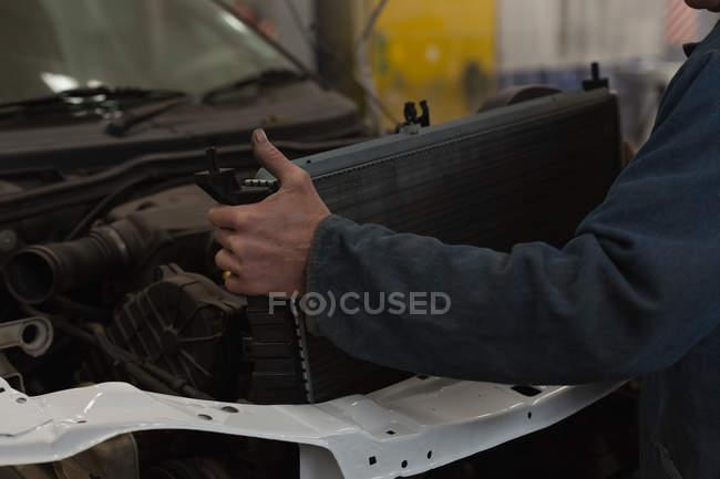 Чоловічий механік розміщення автомобільному радіаторі в Бонні в гаражі — стокове фото