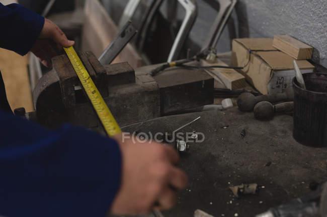 Male mechanic measuring car part in garage — Stock Photo