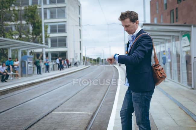 Geschäftsmann checkt Zeit in seiner Smartwatch am Bahnhof — Stockfoto