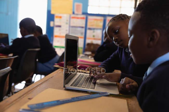 Учащиеся с ноутбуком в классе в школе — стоковое фото