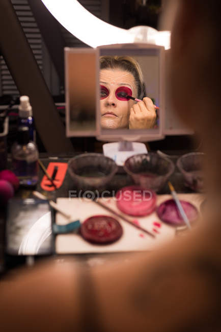 Woman painting her face with brush for halloween celebration — Stock Photo