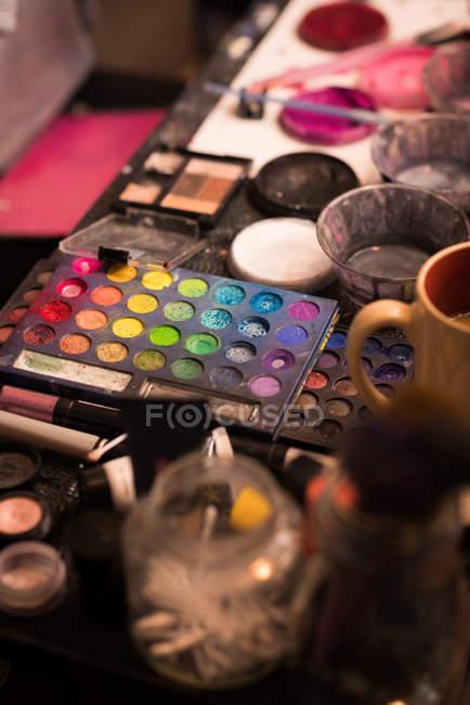 Крупный план различных красок и коробки для макияжа хранится на столе — стоковое фото