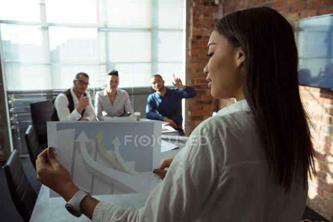 Руководители обсуждения над диаграмма graph в офисе — стоковое фото
