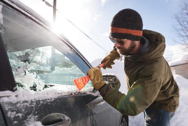 Hombre limpiando nieve del parabrisas del coche durante el invierno - foto de stock