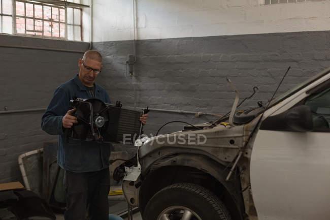 Mâle mécanicien entretien une voiture dans le garage — Photo de stock