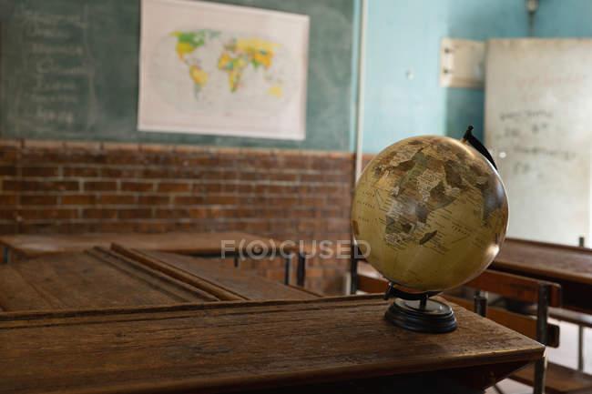 Globe in the empty classroom at school — Stock Photo