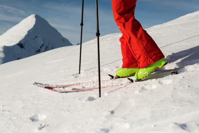 Faible section de skieur masculin marchant avec planche de ski sur une montagne enneigée — Photo de stock