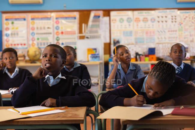 Étudiants qui étudient en classe à l'école — Photo de stock
