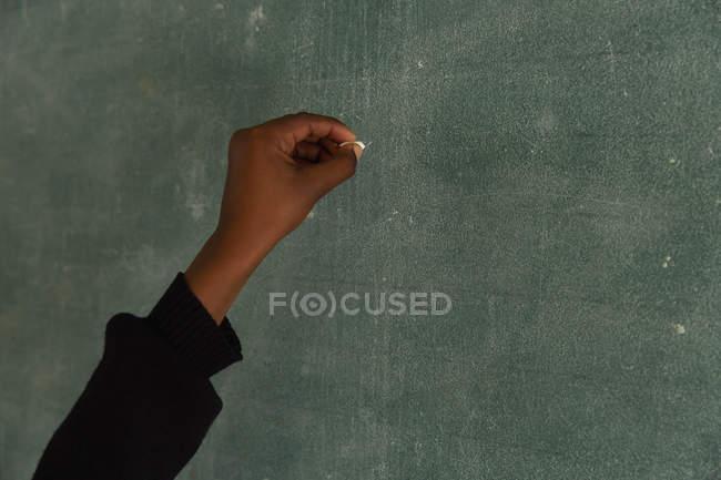 Écrire un écolier sur un tableau en classe à l'école — Photo de stock