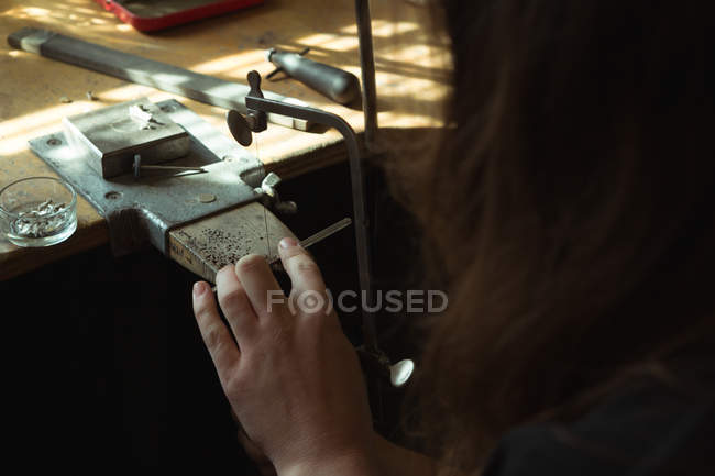 Close-up of jewelry designer using a machine in workshop — Stock Photo
