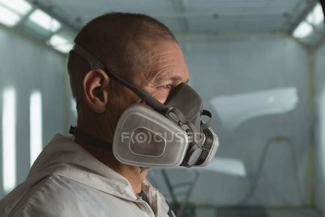 Close-up of mechanic with gas mask in garage — Stock Photo
