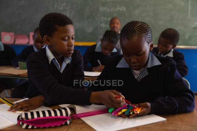 Schoolkids holding sketch pens in classroom at school — Stock Photo