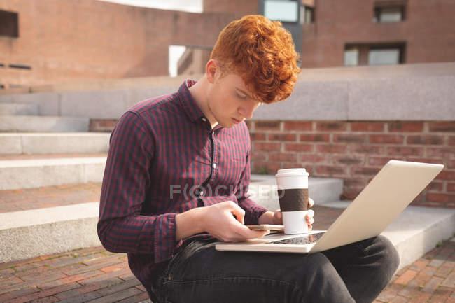 Studente universitario utilizzando il telefono cellulare sulle scale del college — Foto stock