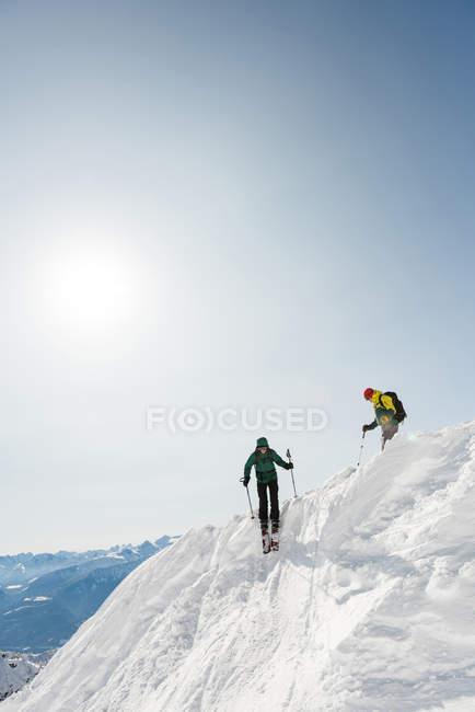 Mâles et femelles skieurs ski sur une montagne enneigée en hiver — Photo de stock