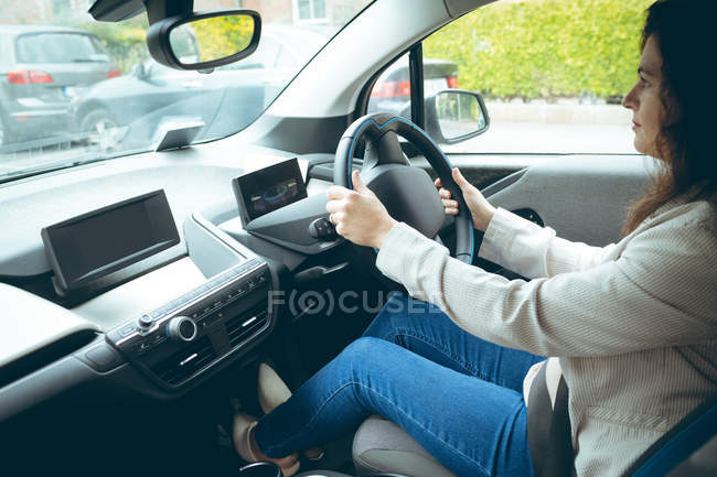 Young businesswoman driving car in city — Stock Photo