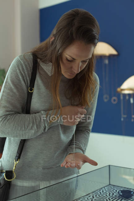 Cliente mujer joven mirando joyas en tienda boutique - foto de stock
