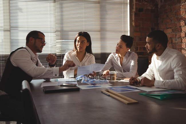 Dirigeants discutant du document dans la salle de conférence au bureau — Photo de stock