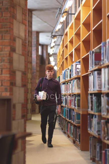 Giovane studente di college con una cammina nella biblioteca di libri — Foto stock