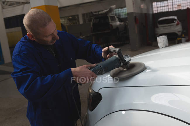 Attentive mechanic polishing car in garage — Stock Photo