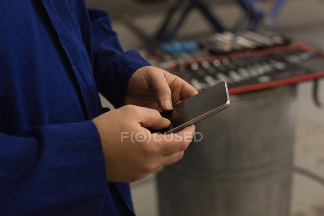 Mid section of male mechanic using mobile phone in garage — Stock Photo