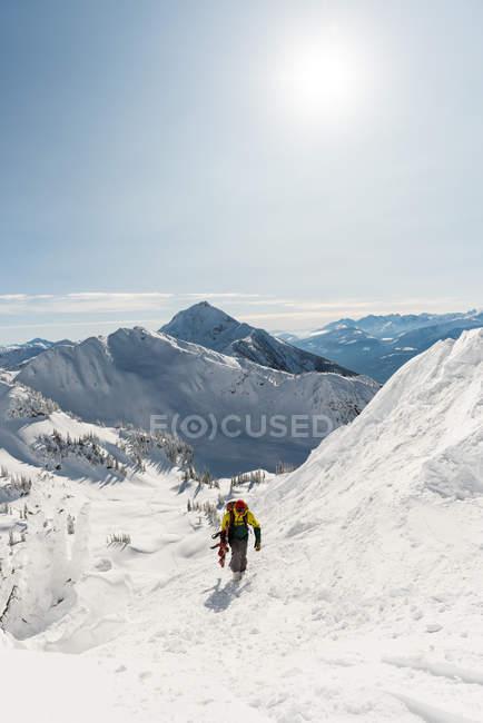 Skieur marchant avec planche de ski sur une montagne enneigée en hiver — Photo de stock