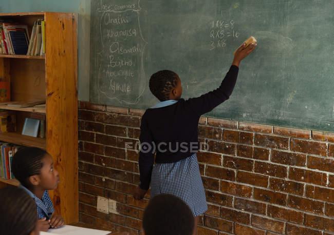 Школьница пишет на доске в классе в школе — стоковое фото