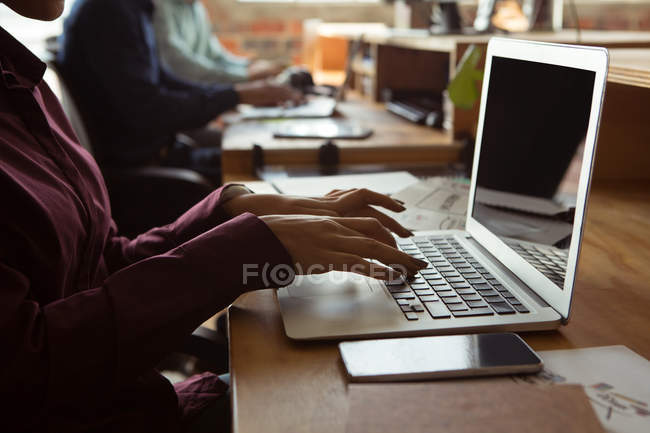Mid section of executive using laptop at desk in office — Stock Photo