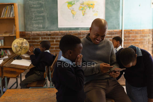 Insegnante di sesso maschile utilizzando tablet digitale con gli studenti in classe a scuola — Foto stock