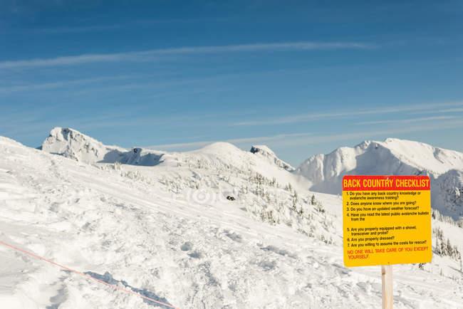 Panneau de signalisation sur un montagnes enneigées en hiver — Photo de stock