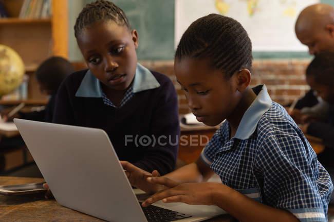 Школярі, використовуючи ноутбук у класі в школі — стокове фото