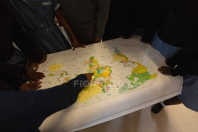 Schoolkids looking at world map in classroom at school — Stock Photo