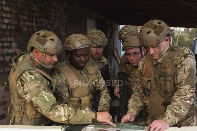 Military men discussing the map during military training — Stock Photo