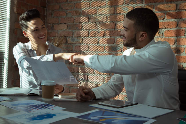 Executives celebrating success with fist bump in office — Stock Photo
