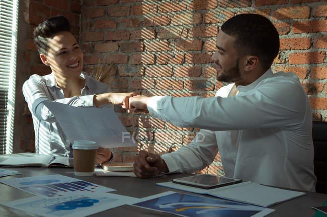 Executivos, comemorando o sucesso com punho solavanco no escritório — Fotografia de Stock