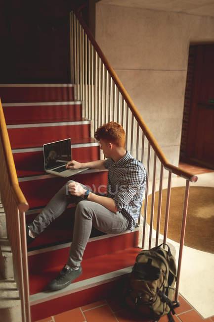 Étudiant utilisant un ordinateur portable sur les escaliers du campus — Photo de stock