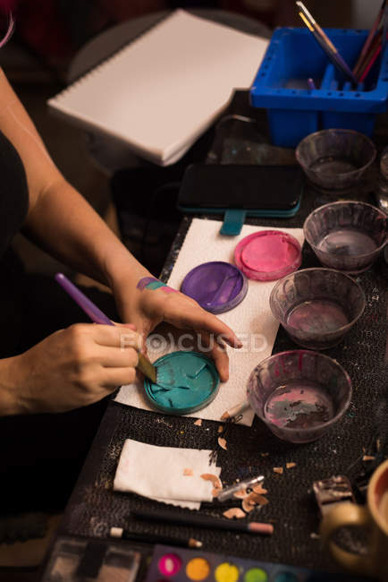 Mid section of woman mixing paint with brush — Stock Photo