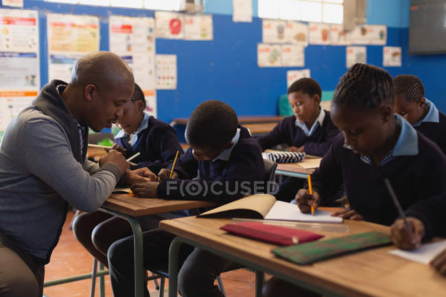 Male teacher teaching students in the class at school — Stock Photo