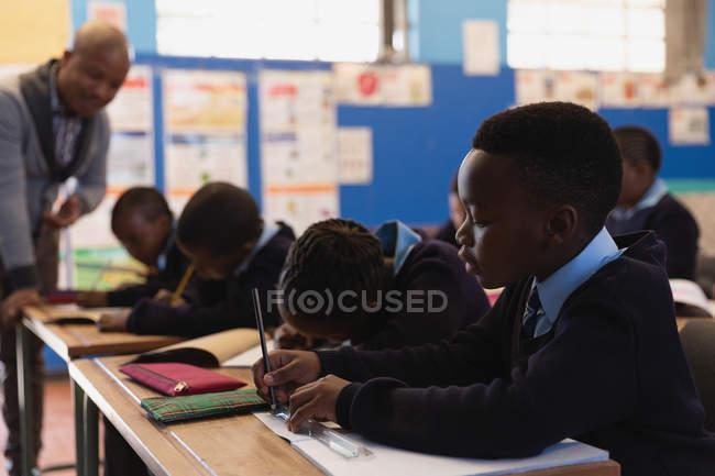 Enseignant de sexe masculin élèves dans la classe à l'école — Photo de stock