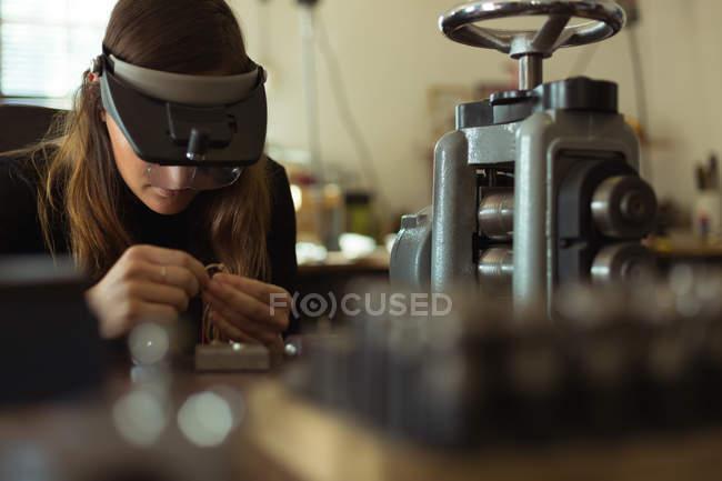 Женщина-дизайнер ювелирных изделий работает в мастерской — стоковое фото