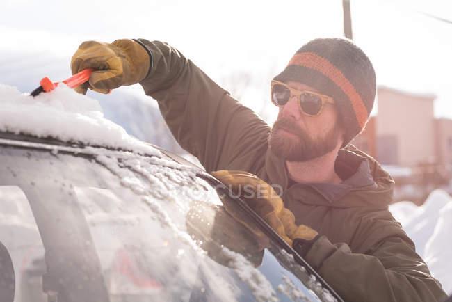 L'homme de neige nettoyage du pare-brise de la voiture en hiver — Photo de stock