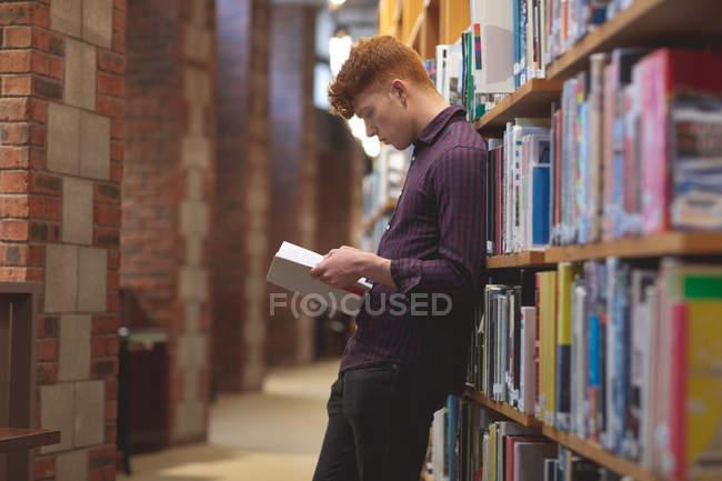 Vista laterale di studente di college che legge un libro in libreria — Foto stock