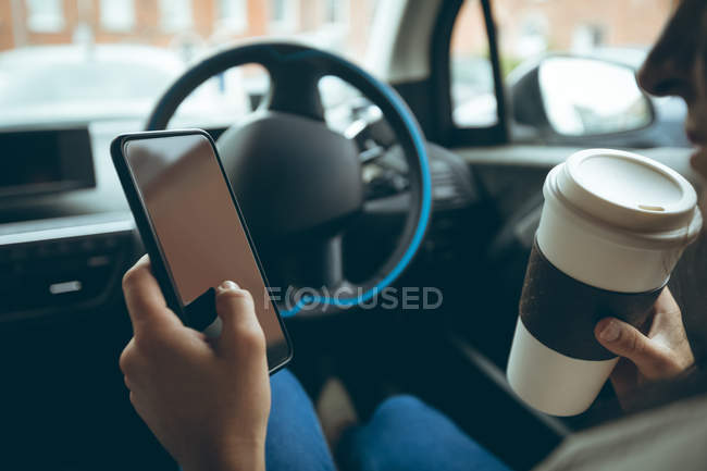 Businesswoman using mobile phone while having coffee in a car — Stock Photo