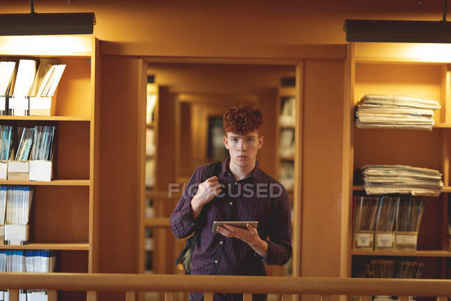 Étudiant avec tablette numérique regardant la caméra dans la bibliothèque — Photo de stock