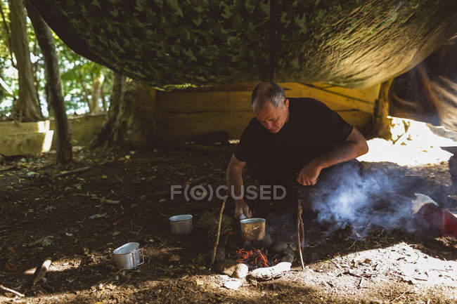 Fit man cuisson des aliments au camp de démarrage — Photo de stock