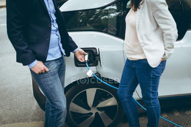 Section médiane de collègues de travail, voiture électrique à la station de recharge de charge — Photo de stock