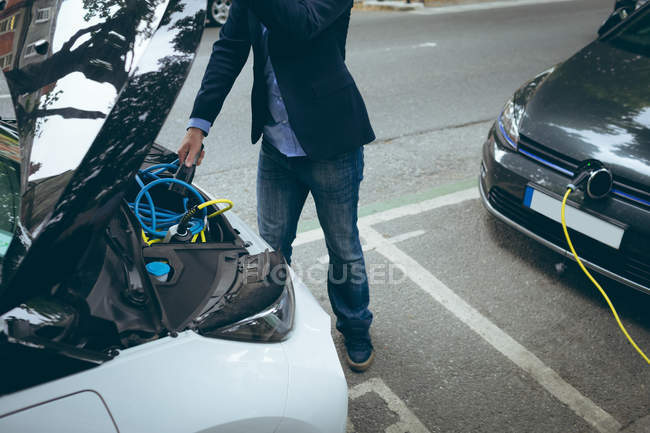 Faible section d'homme d'affaires, voiture électrique à la station de recharge de charge — Photo de stock