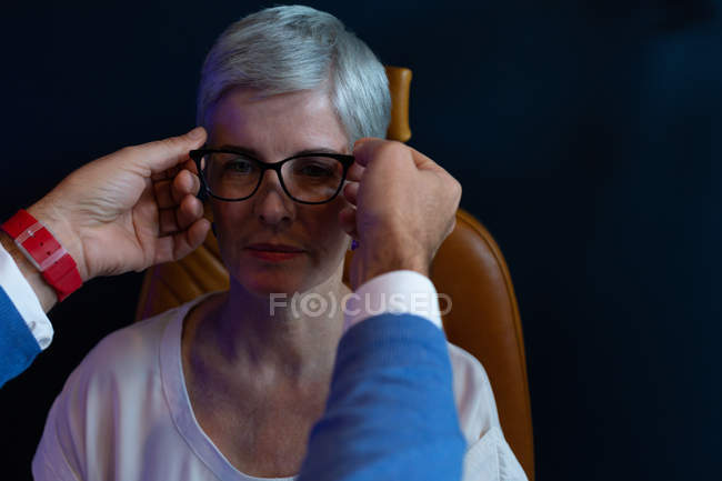 Optometrist adjusting eyeglasses on patient eyes in clinic — Stock Photo