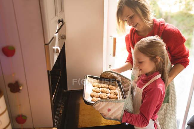 Mère et fille regardant les biscuits cuits dans la cuisine — Photo de stock