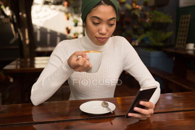 Красива жінка, що використання мобільного телефону під час за кавою в кафе — стокове фото