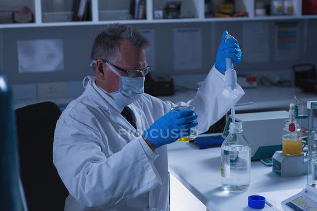 Scientifique masculin attentif expérimentant en laboratoire — Photo de stock